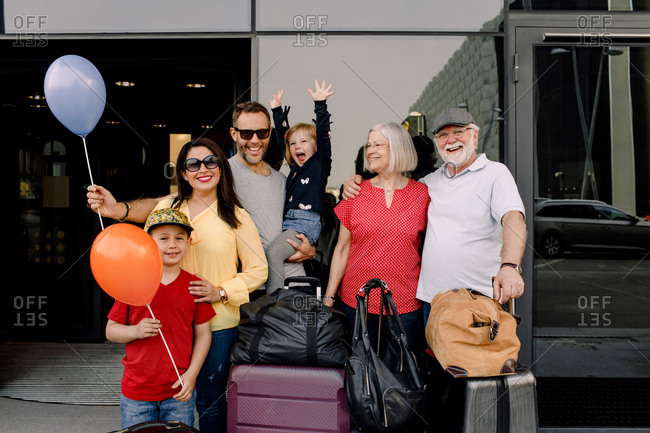 Portrait of cheerful family with luggage standing at hotel entrance during vacation