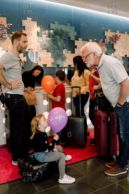 Grandfather talking to girl holding balloon while sitting on suitcase in hotel