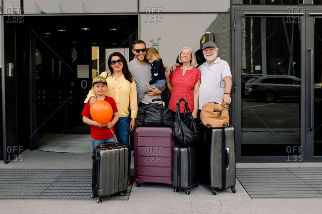 Portrait of happy family with luggage standing at hotel entrance