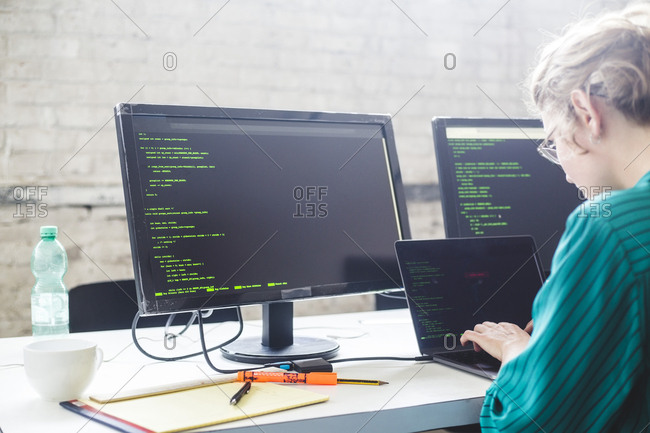 Side view of businesswoman working on start-up project while coding in office