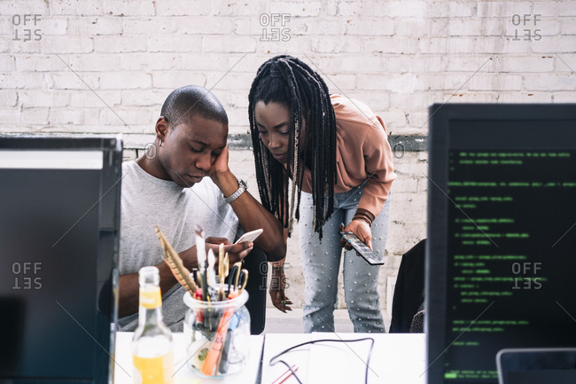 Young businesswoman looking at businessman using smart phone in creative office
