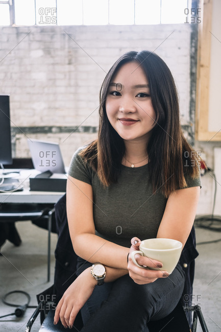 Portrait of smiling female computer programmer holding coffee cup while sitting at creative office