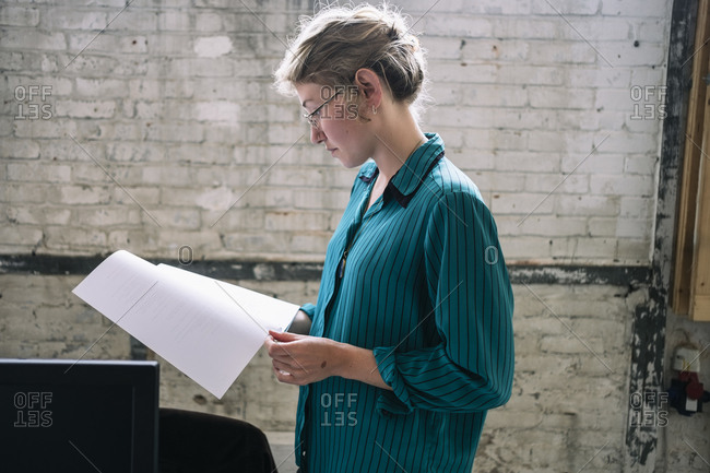 Confident young female IT professional reading document standing at creative workplace