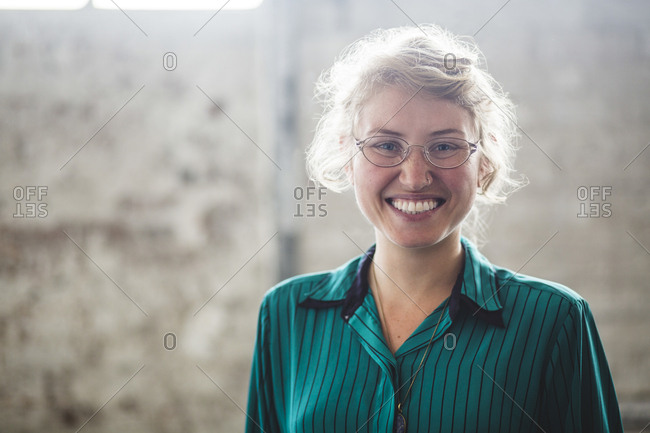Portrait of smiling blond female programmer standing at creative office