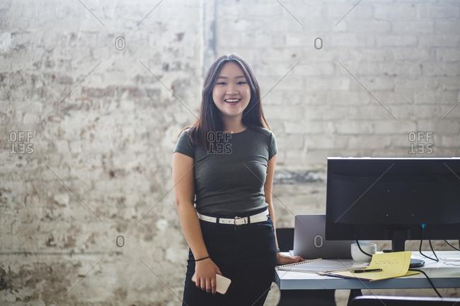 Portrait of smiling female computer programmer standing beside desk at creative office