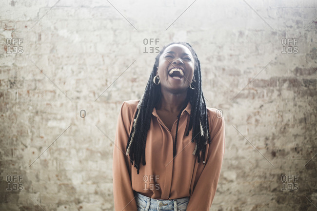 Female computer hacker with dreadlocks laughing against wall in office