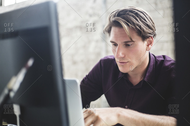 Male computer programmer using laptop while working in office