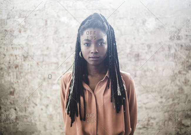 Portrait of confident female programmer with dreadlocks standing against wall in office