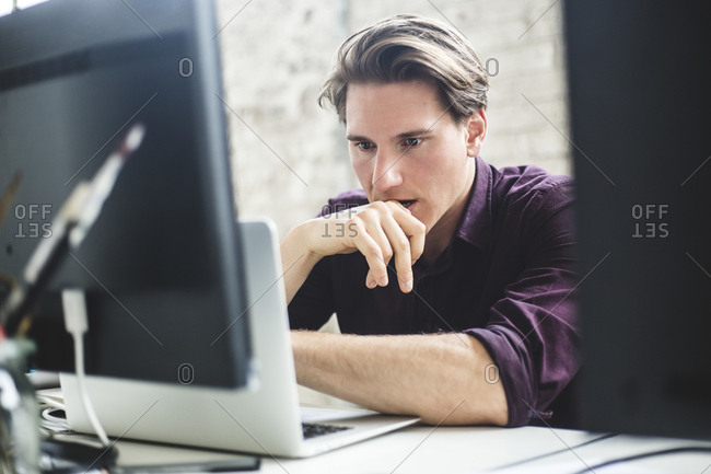Serious male IT professional thinking while coding in laptop at creative workplace