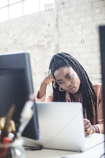 Thoughtful female programmer looking at laptop while working in office