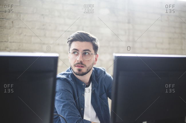 Young entrepreneur looking away while working on computer programs in creative office