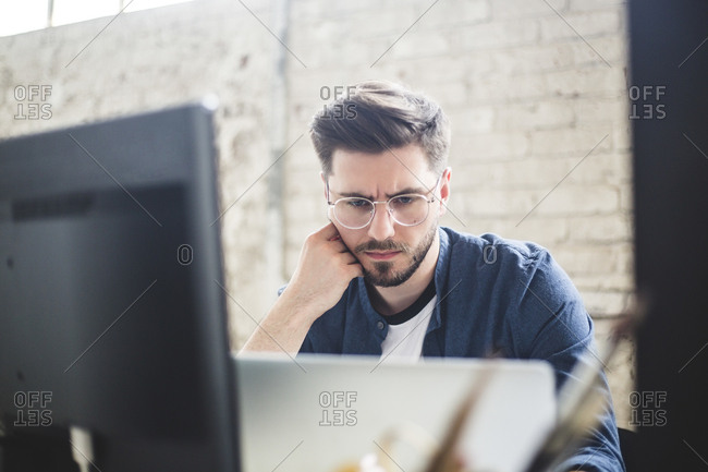 Male IT professional thinking while working on computer codes in laptop at workplace
