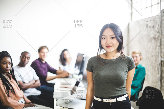 Portrait of smiling female IT expert with coworkers in background at workplace