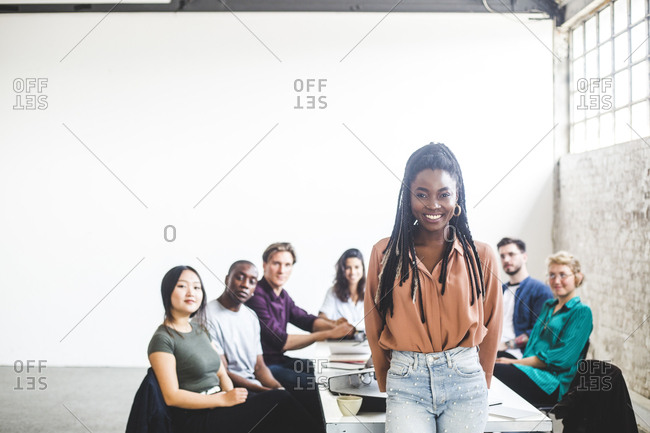 Portrait of cheerful businesswoman working with computer programmers in board room