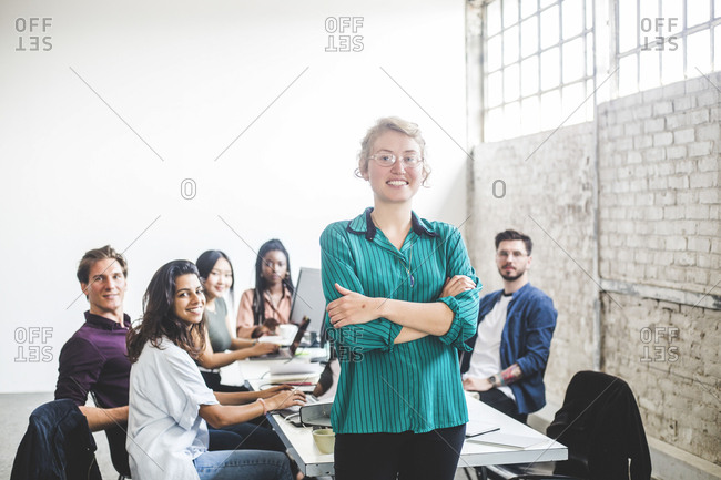 Portrait of confident smiling female programmer with colleagues working in board room