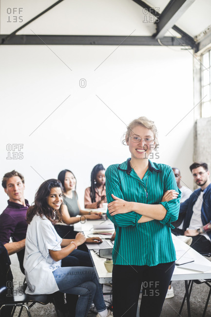 Portrait of smiling female computer hacker with arms crossed standing against team at workplace