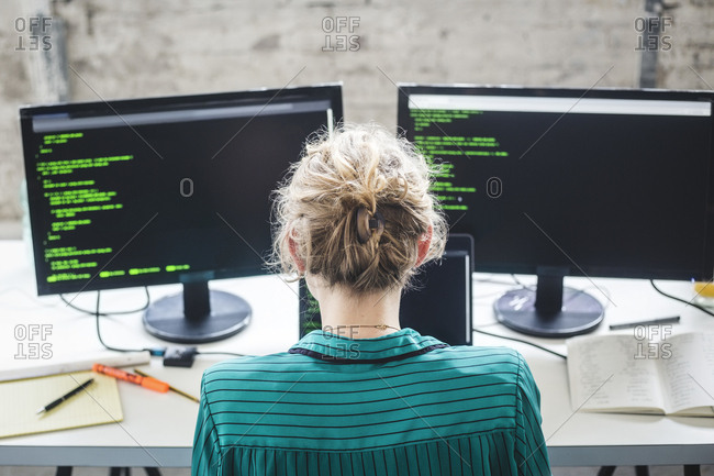 High angle view of female IT expert working on computer programs at desk in creative office