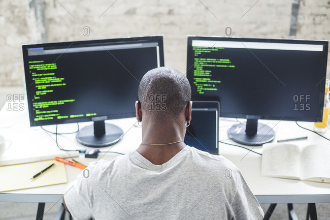 High angle view of shaved head computer programmer programming codes at desk in office