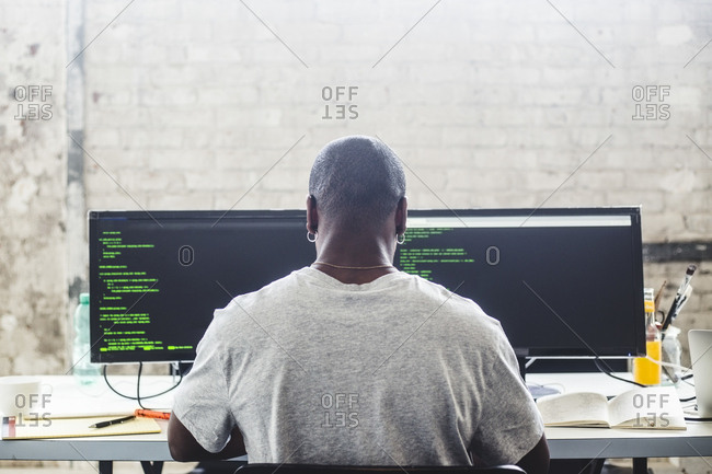 Rear view of male IT expert using computer while coding at creative workplace