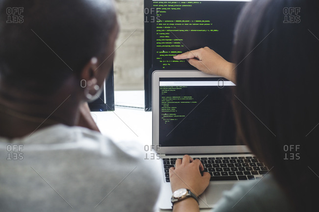 Rear view of female entrepreneur pointing at codes on computer monitor to male hacker in office