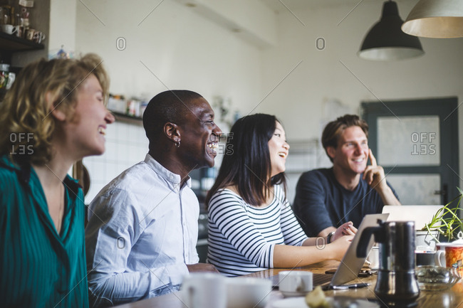 Smiling entrepreneurs sitting while looking away at desk in office