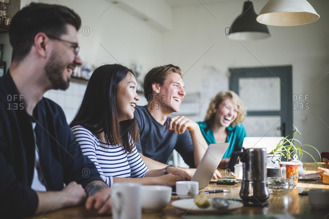 Team of professional computer hackers laughing while sitting at desk in office