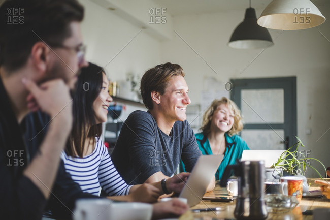 Happy computer programmers looking away while working at table in office