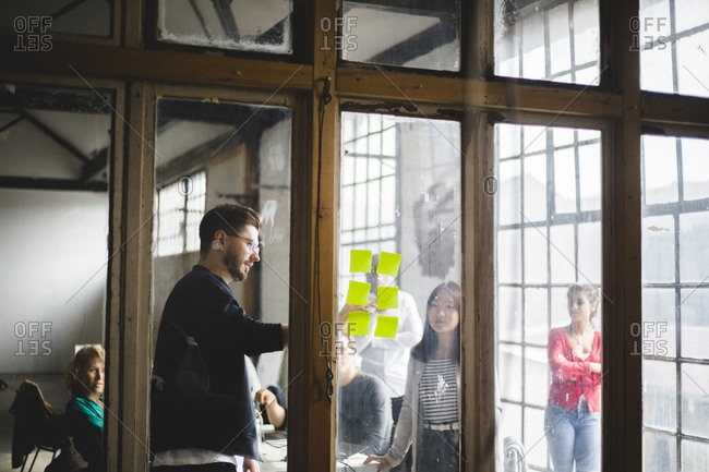 Young male IT programmer sharing business ideas with team while pointing at adhesive notes seen through glass wall in of
