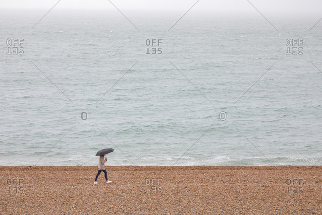 Single young lady walking in rain on stormy day, Brighton, England