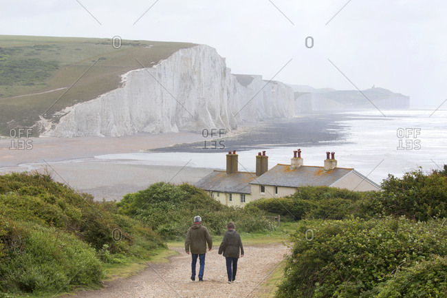 Couple hiking a trail by Seven Sisters Cliffs, Brighton, England