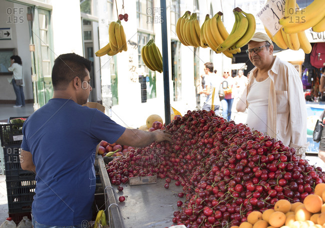 Athens, Greece - June 5, 2019: Man selling cherries and other fruits in Agora marketplace