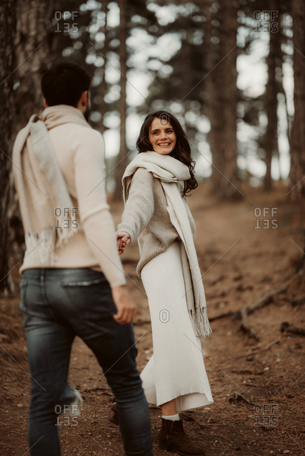 Young couple walking hand in hand through a forest