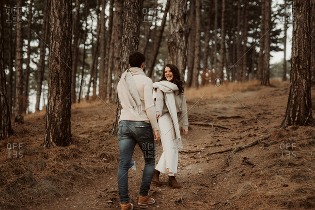 Couple walking hand in hand through a forest and laughing