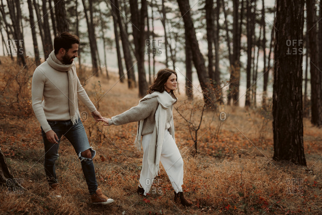 Young couple walking hand in hand through a foggy forest