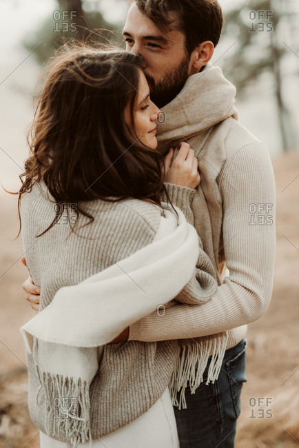 Couple hugging in a foggy forest