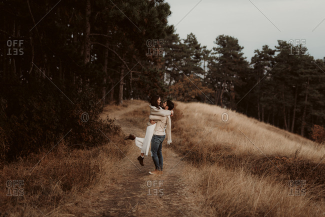 Man playfully picking up his lover while walking in the forest