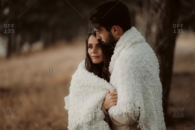 Couple cuddling under warm blanket