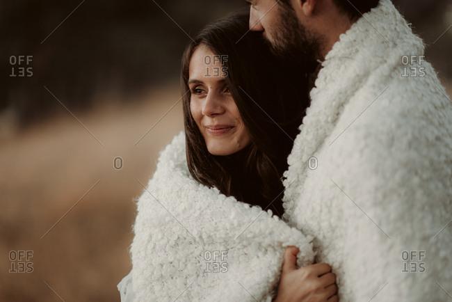 Close up of couple cuddling under warm blanket
