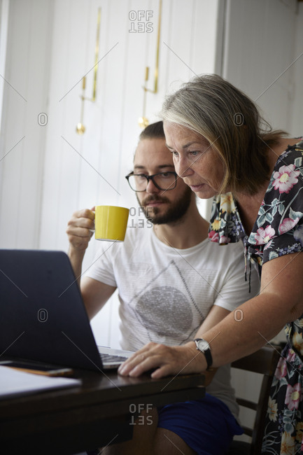 Senior woman using laptop with adult son