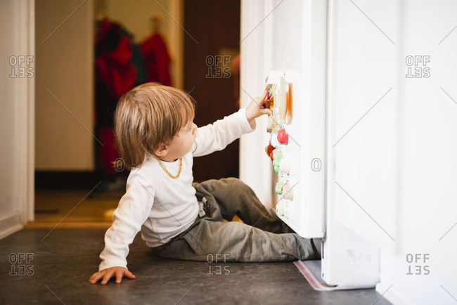 Boy playing with fridge magnets