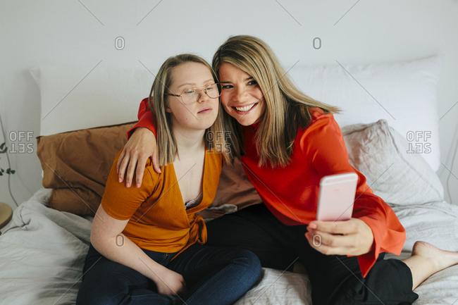Sisters on bed taking selfie
