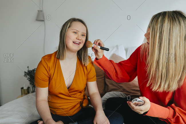 Sisters having make-up on bed