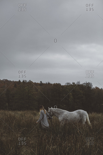 Woman walking with horse through meadow