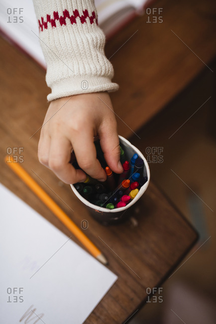 Childs hand choosing crayon