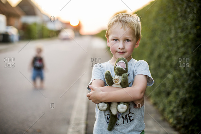 Boy holding stuffed dinosaur