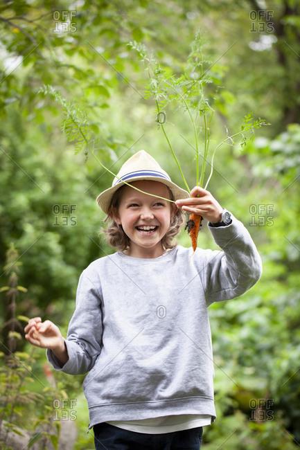 Smiling girl holding carrot