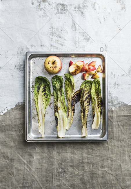 Grilled greens and apples on baking tray