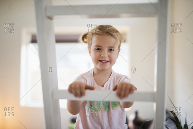 Girl on ladder looking at camera