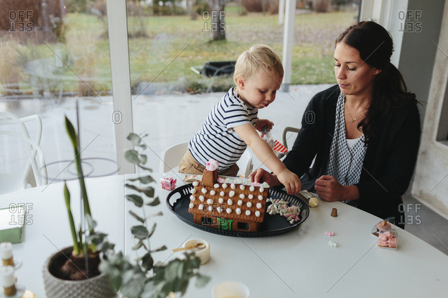 Mother with son decorating gingerbread house