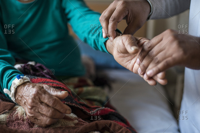 A doctor checks a patients pulse in a hospital in Nepal